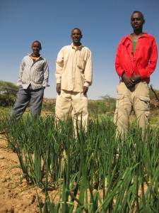 Ferhan (center) stands with fellow farmers from Ruqi who are learning new techniques on the demonstration plot.